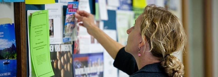 A student is searching new notice on the notice board